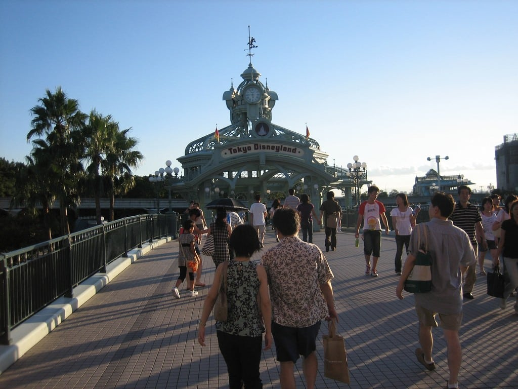 Tourists walk into Tokyo Disneyland, whose third quarter earnings exceeded forecasts on visitor numbers.
