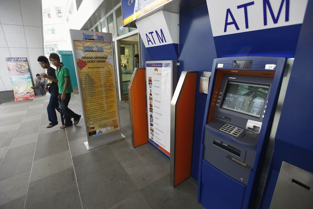 People walk past ATM machines at a shopping centre in Yangon, in this May 27, 2012 file photo.