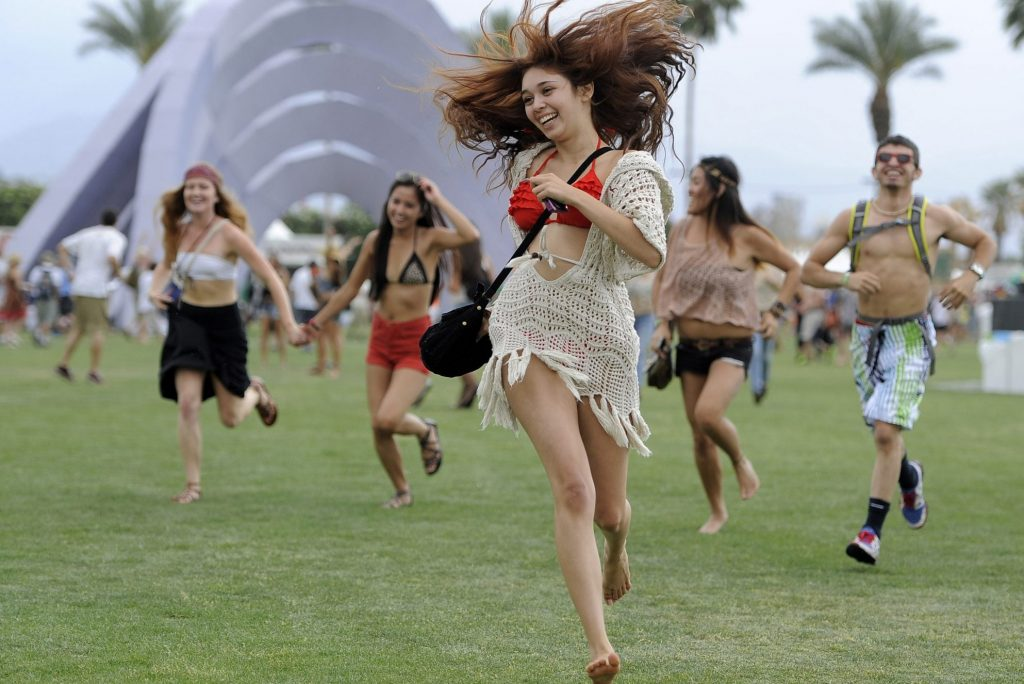 This April 13, 2012 photo shows festivalgoers running toward the main stage to catch the beginning of Kendrick Lamar's set during the first weekend of the 2012 Coachella Valley Music and Arts Festival in Indio, California. Music is playing an increasing role in travel plans.