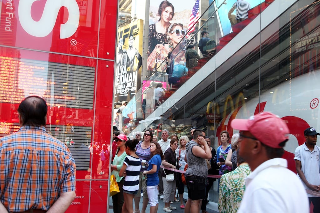 This June 19, 2013 photo shows crowds gathering outside the TKTS booth in Times Square in New York. The booth, which offers same-day discount Broadway and off-Broadway tickets, turns 40 this summer.
