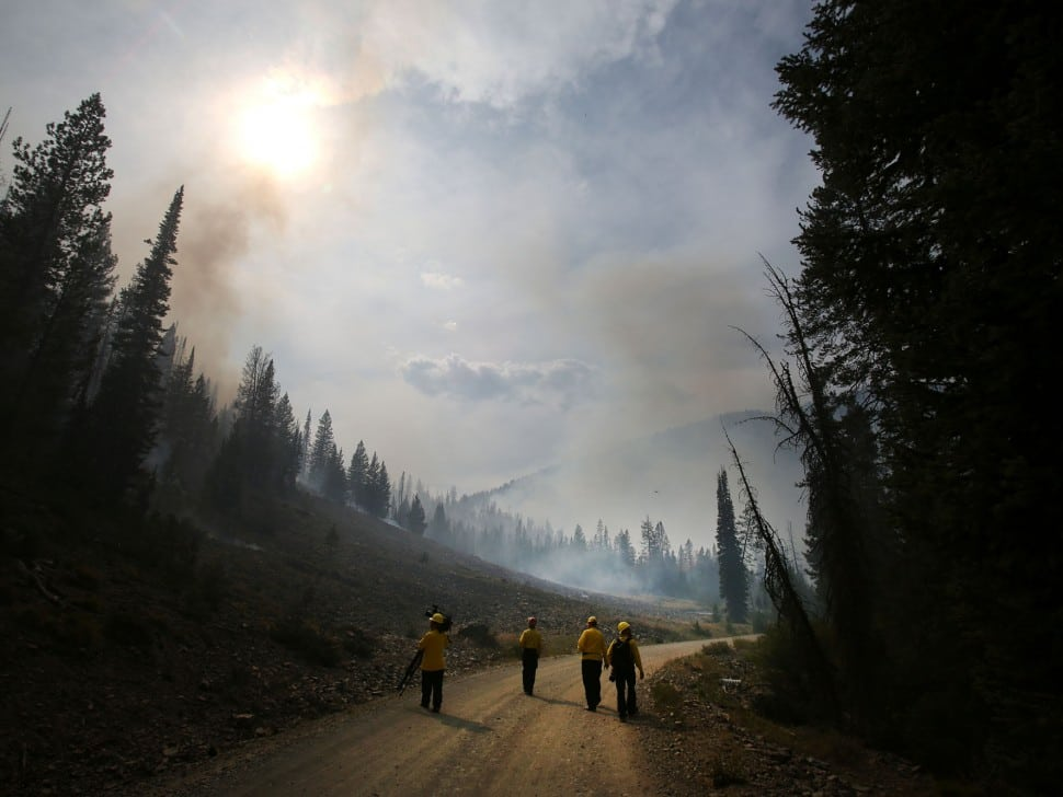 "In this Aug. 19, 2013 file photo, members of the media walk through part of the 104,457 acres Beaver Creek Fire in the Baker Creek area north of Ketchum, Idaho. With its mountain backdrop, Sun Valley is normally a playground for the rich, the famous, for super-fit pursuers of outdoor sports or the Big Wood River's feisty brook trout. To many, it's heaven. But the fire known as ""the Beast"" has raised hell with the sun-basking, fun-loving lifestyle."