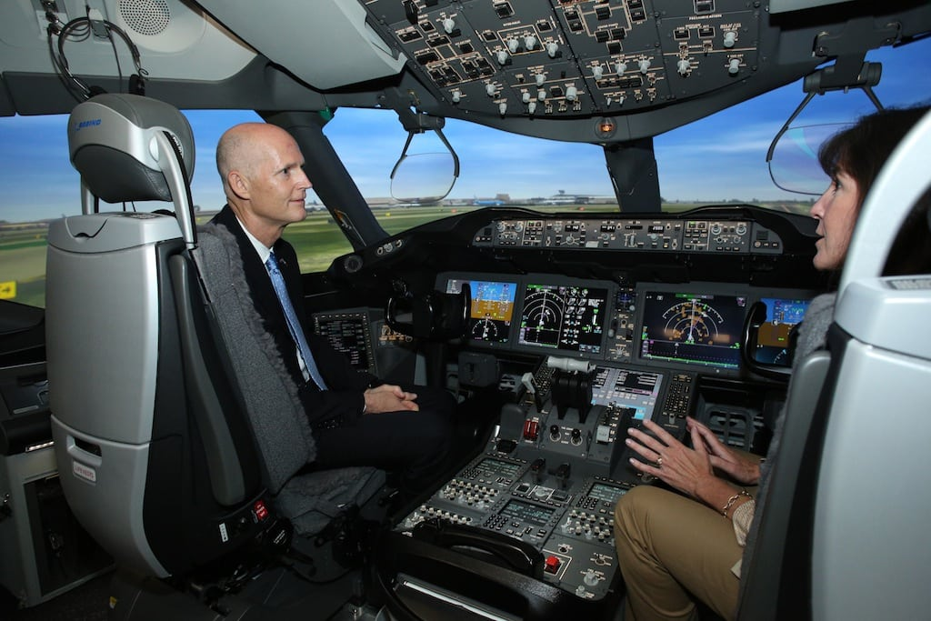 Florida Governor Rick Scott and Boeing Vice President Sherry Carbary talk inside the 787 simulator at the Miami campus.