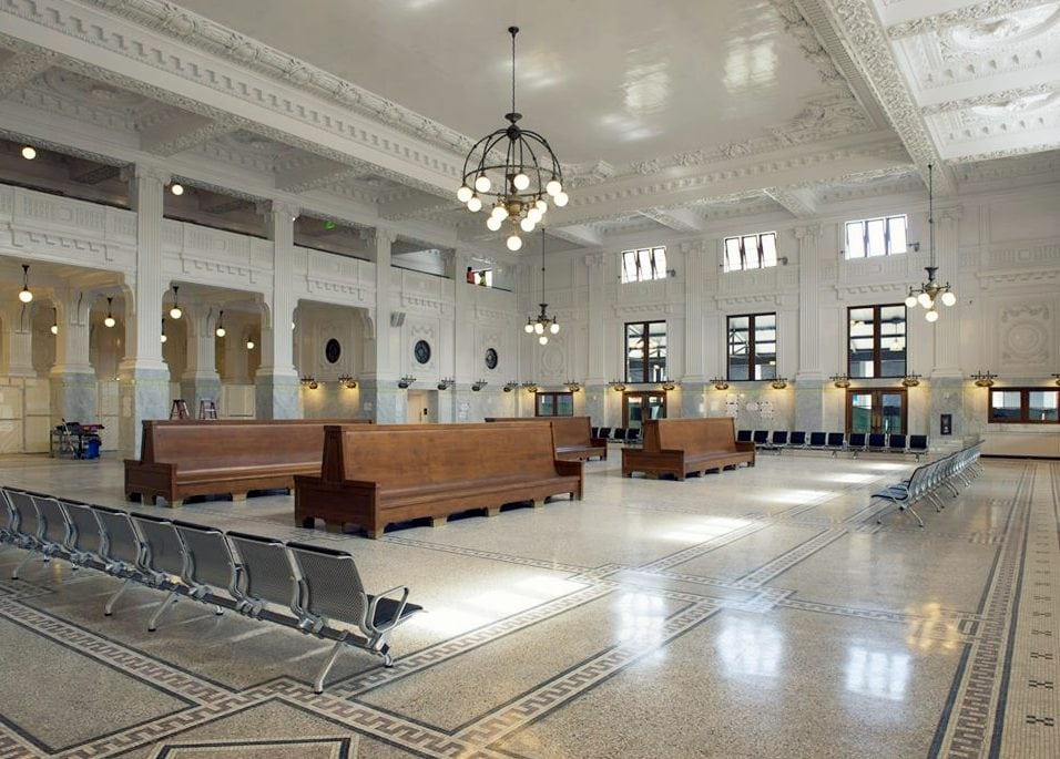 King Street Station, Seattle: Inside the main entry, at the base of the clock tower, is the entry hall, known as the Compass Room. The name references the navigational star compass rose design laid out in hand-cut marble tiles on the floor at its center. The Compass Room has marble wainscotting, and is lighted by a multi-globe chandelier suspended above the compass rose from an elaborate plaster rosette.
