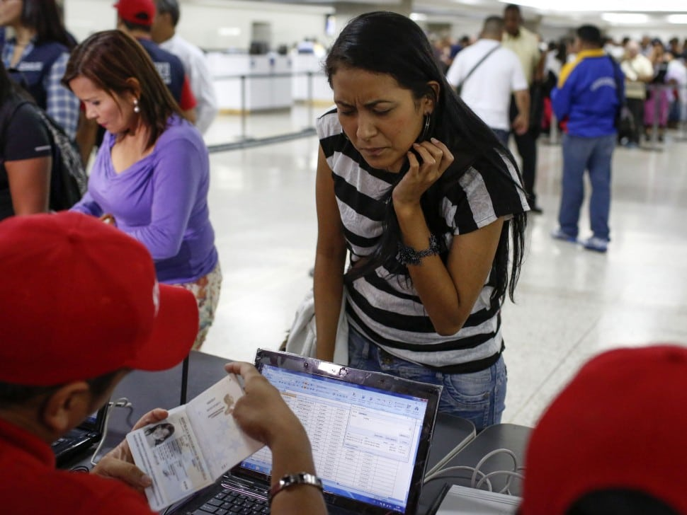 A passenger presents her documents at a special check point of the state currency board Cadivi in the Simon Bolivar airport in La Guaira, outside Caracas October 15, 2013. President Nicolas Maduro's government plans to use fingerprint machines at airports to try to root out no-shows who buy tickets to scam travel-related currency controls without even flying, in the latest symptom of Venezuela's economic chaos.