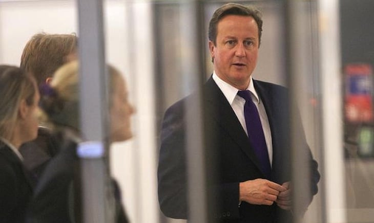 Britain's Prime Minister David Cameron watches passengers pass through immigration control during a visit to Terminal 5, at Heathrow Airport, west of London October 10, 2011.