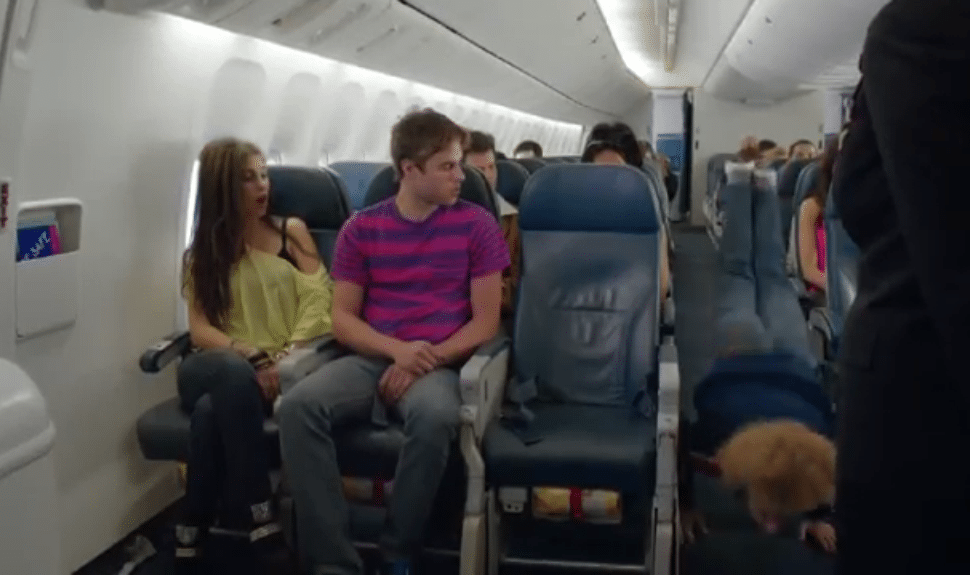 """The man in the aisle is doing """"the worm,"""" a popular breakdance move."""