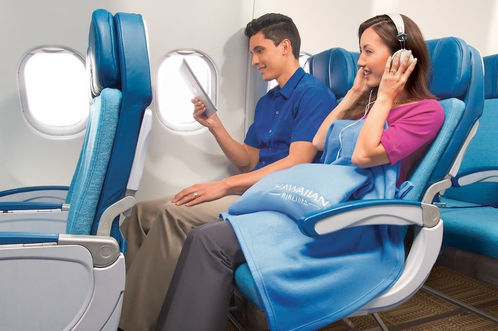 A couple in coach class on Hawaiian Airlines.  A UK regulatory body blocked the Sabre-Farelogix merger on the basis of it hurting innovation for travel agencies seeking to offer extra legroom seats, meals and Wi-Fi to airline passengers.