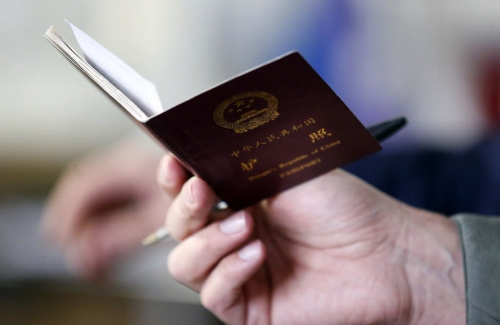 A police officer checks a Chinese passport in Prato, Italy.