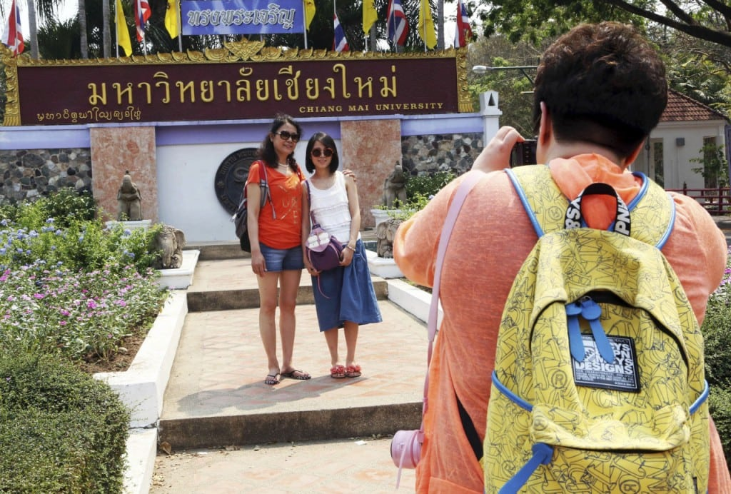 Advance for Thailand Challenging Chinese, in this photo taken March 30, 2014, Chinese tourists pose for photograph at the main entrance to Chiang Mai university in Chiang Mai province, northern Thailand.