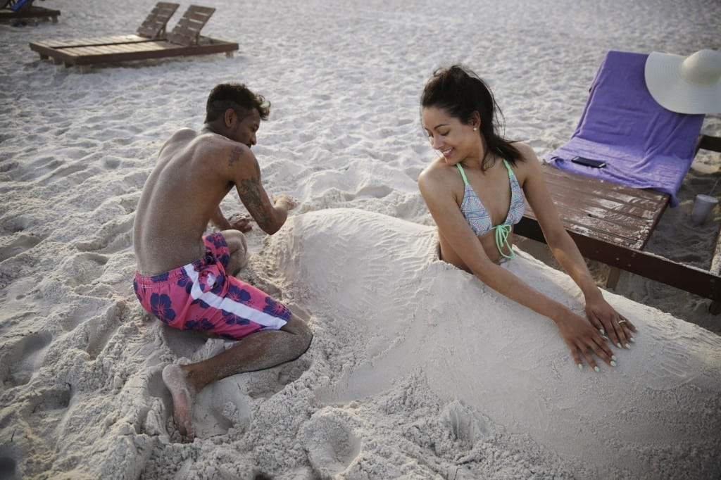 Demarkis Mosley, left, and his wife, Alexandria, of Starkville, Miss., play in the sand on their vacation in Gulf Shores, Ala.