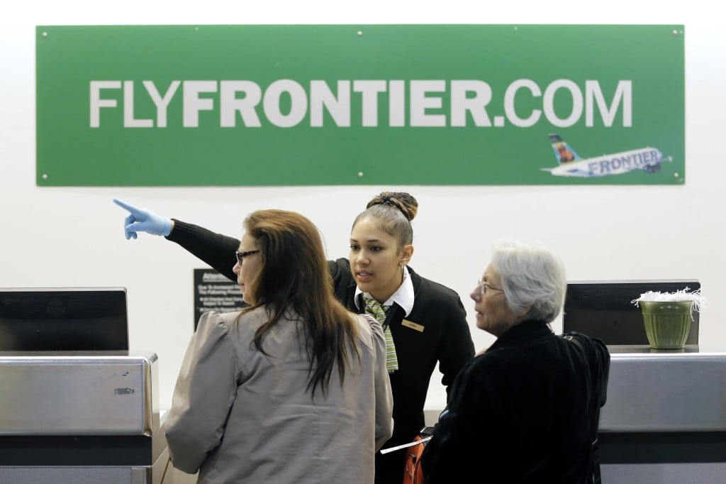 In this October 2014 photo, a Frontier Airlines employee directs passengers at Cleveland Hopkins International Airport in Cleveland. Many travelers have been continuing to buy frequent flier miles and hotel points, providing options to help cash-starved airlines and hotels.