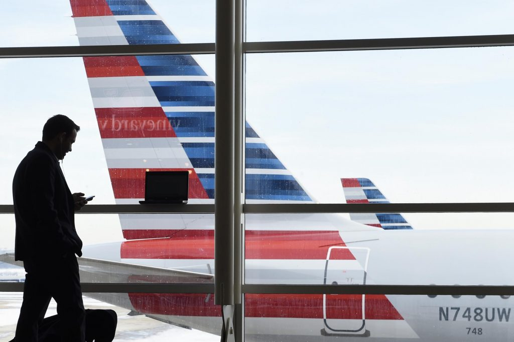 A passenger uses the phone at Washington's Ronald Reagan National Airport. This year, technology in corporate travel is undergoing massive change.