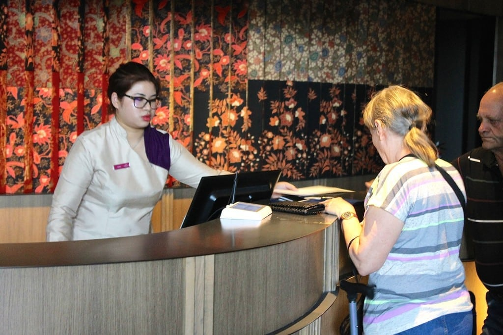 A front desk employee at the Crown Plaza Changi Airport in Singapore helps guests check-in to their room.