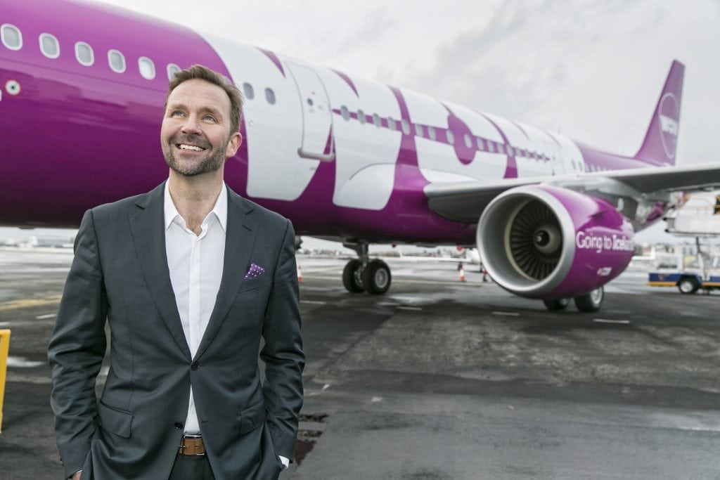 Wow Air founder Skúli Mogensen stands in front of one of his company's Airbus aircraft. Wow is facing increased competition on key routes.
