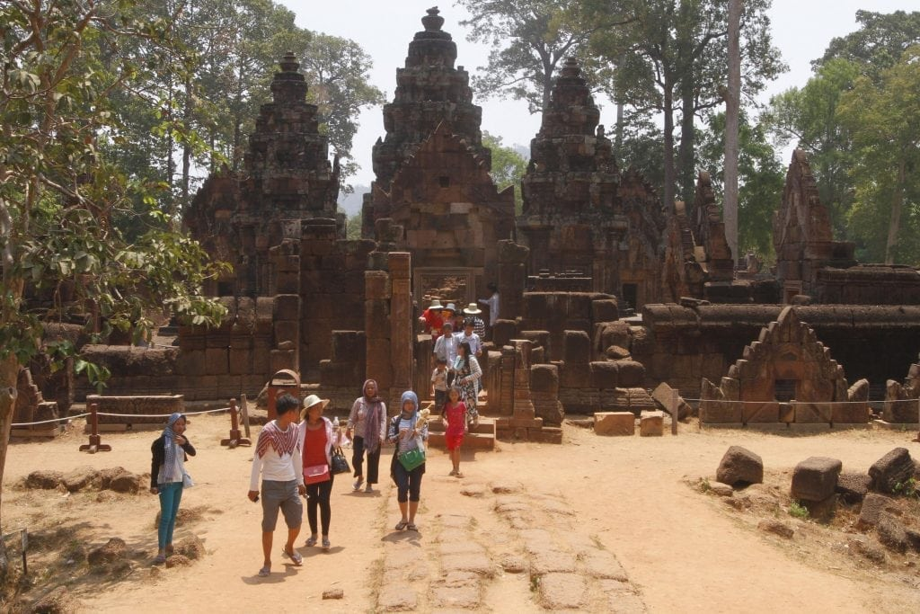In this April 15, 2016 photo, tourists walk at Banteay Srey temple of Angkor complex, in Siem Reap province, about 320 kilometers (199 miles) north of Phnom Penh, Cambodia. Visitors who dress immodestly will not be allowed to enter Cambodia's famed Angkor temple complex, the agency that oversees the site said July 7, 2016.