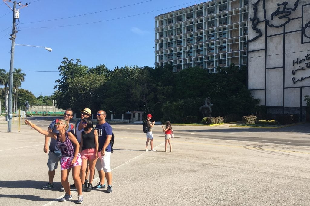 A group of tourists in Havana, Cuba pose for a selfie in front of the Ministry of Intelligence. The surge of American tourists to the country is already in jeopardy.