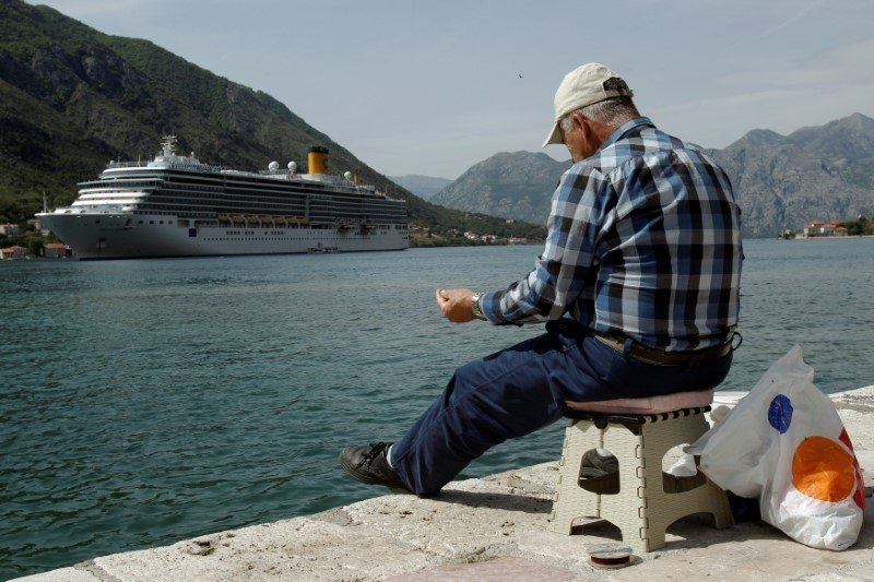 A man fishes in front of a cruiser ship at UNESCO protected Region of Kotor, Montenegro April 27, 2017. This UNESCO status is in possible jeopardy.