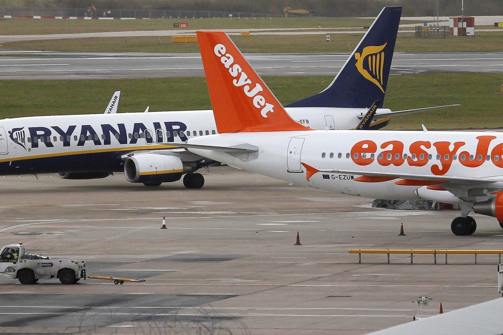 A Ryanair aircraft taxis past an Airbus A320-214 aircraft, operated by EasyJet Plc, at Manchester airport in Manchester, UK, on January 29, 2013. Both low-cost carriers remain competitive.