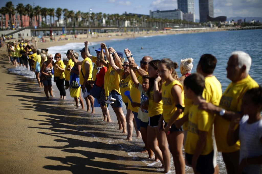 In this August. 12, 2017 file photo, people form a human chain during a protest against tourism in Barcelona, Spain. Global destinations have woken up to the danger of overtourism.