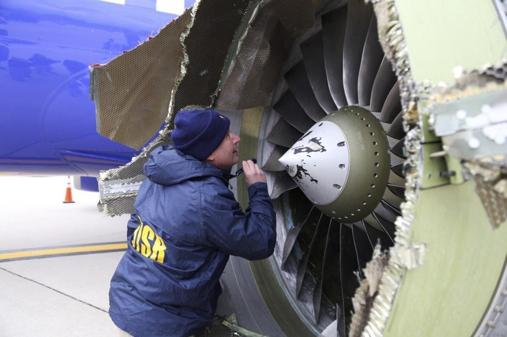 In this Tuesday, April 17, 2018 photo, a National Transportation Safety Board investigator examines damage to the engine of the Southwest Airlines plane that made an emergency landing at Philadelphia International Airport in Philadelphia. A preliminary examination of the blown jet engine of the Southwest Airlines plane that set off a terrifying chain of events and left a businesswoman hanging half outside a shattered window showed evidence of