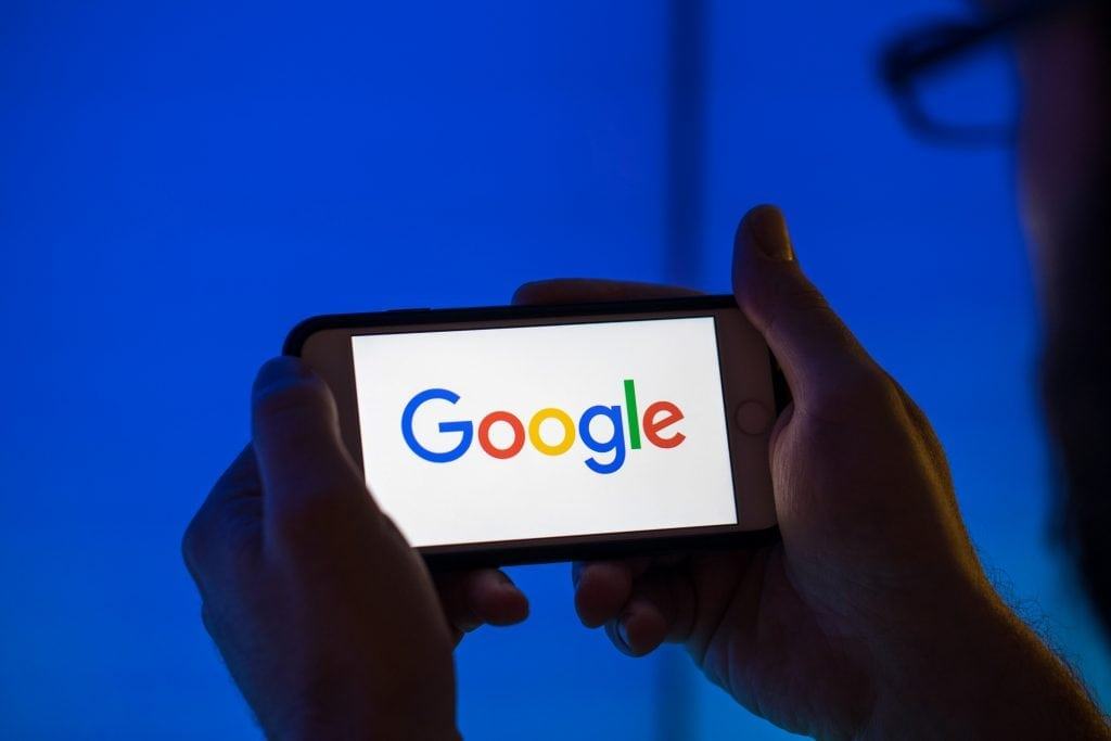 Google's logo is shown on a smartphone. The search giant gives preference to its own travel business, but claims of political bias are unfounded.