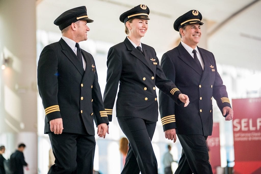 Three Delta Air Lines pilots walk through an airport. The carrier's pilot union is concerned about the airline's joint ventures.
