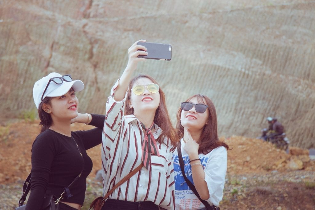 Millennial and Gen Z travelers from India and China are avid and optimistic travelers. In the photo, three young women take a selfie on a smartphone.