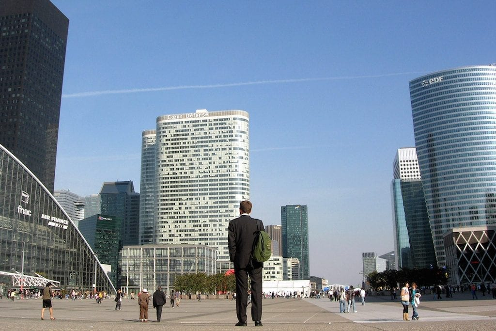A business traveler stands in the neighborhood of La Défense. Located on the outskirts of Paris, it's one of the largest business districts in Europe. Corporate travel management startups aim to keep travelers happy by focusing on perks.