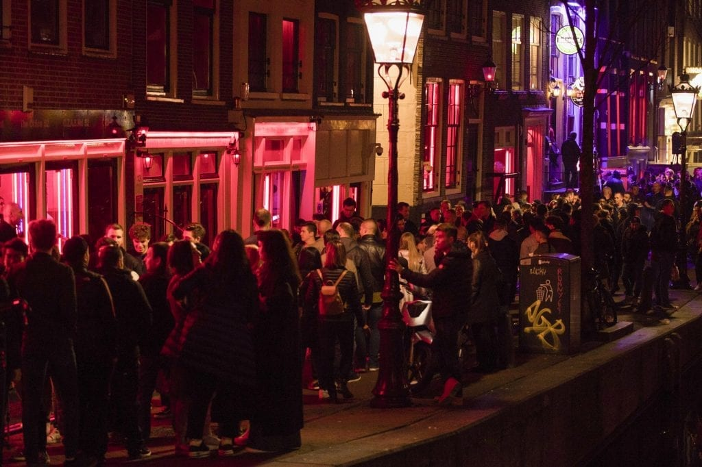 A mob of tourists gather around a window in Amsterdam's red light district.