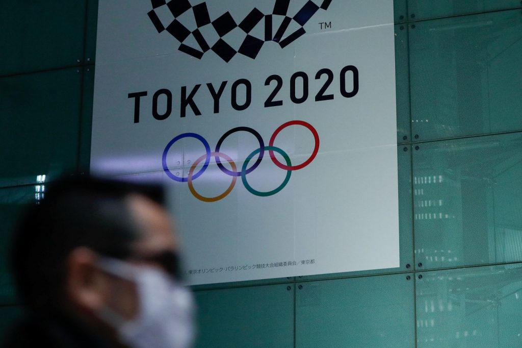 A man wearing a protective face mask following an outbreak of the coronavirus disease (COVID-19) walks past a banner for the upcoming Tokyo 2020 Olympics in Tokyo, Japan, March 11, 2020.