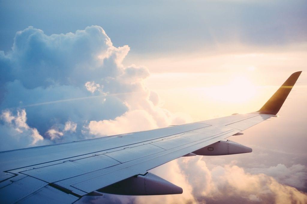 An aircraft flying through clouds carries passengers to their subscription travel destination.